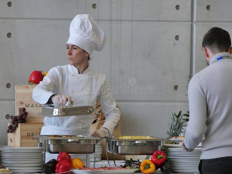 Professional female chef prepares buffet food for customers stock photos