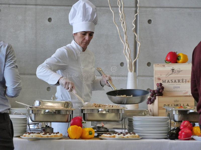 Professional female chef prepares buffet food for customers royalty free stock photo