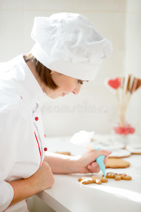 Professional female confectioner bent decorating a gingerman stock images