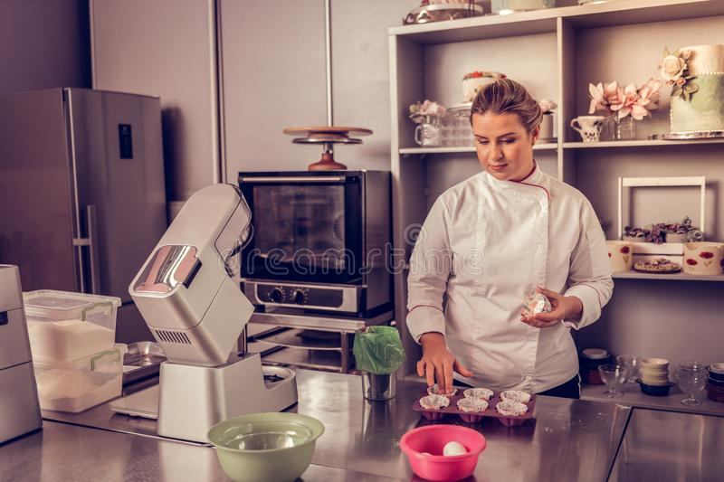 Professional female cook standing in her kitchen royalty free stock image