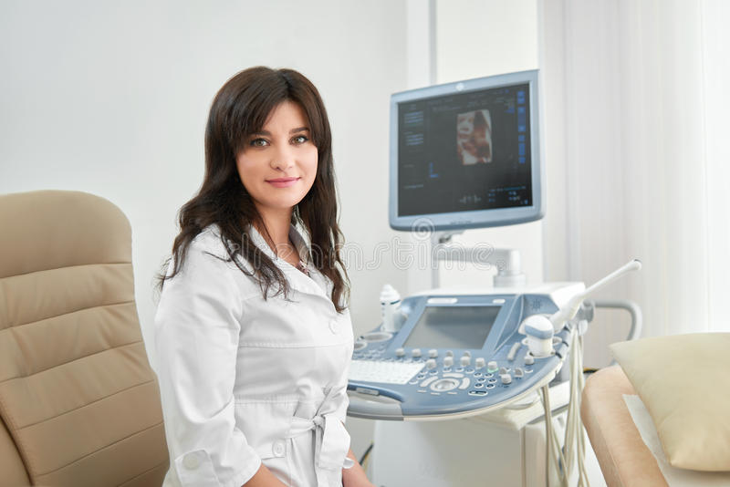 Professional female doctor against ultrasound equipment with computer. Professional in white uniform in modern clinic smiling at camera. Attractive brunette royalty free stock photography