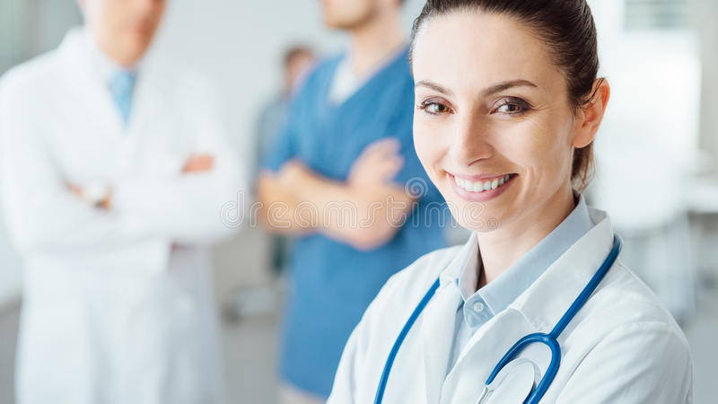 Professional female doctor posing and smiling royalty free stock photo
