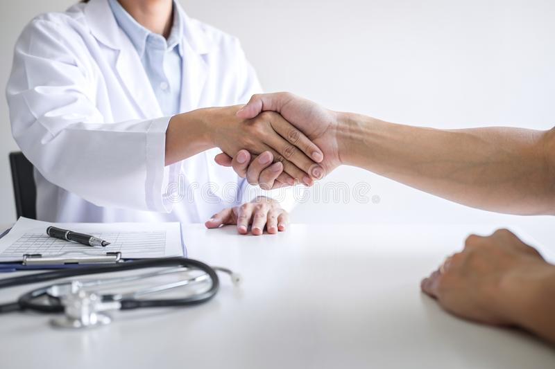 Professional female doctor in white coat shaking hand with patient after successful recommend treatment methods after results stock images