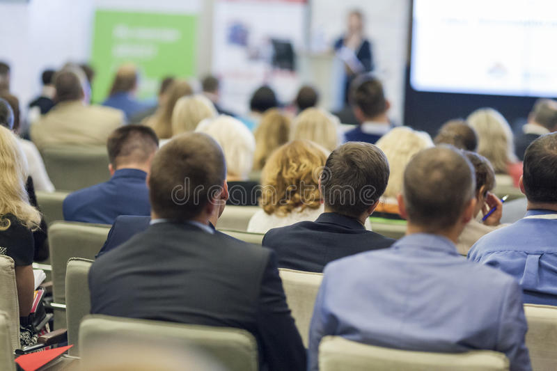 Professional Female Host Speaking in Front of the Large Audience During Business Conference. royalty free stock images