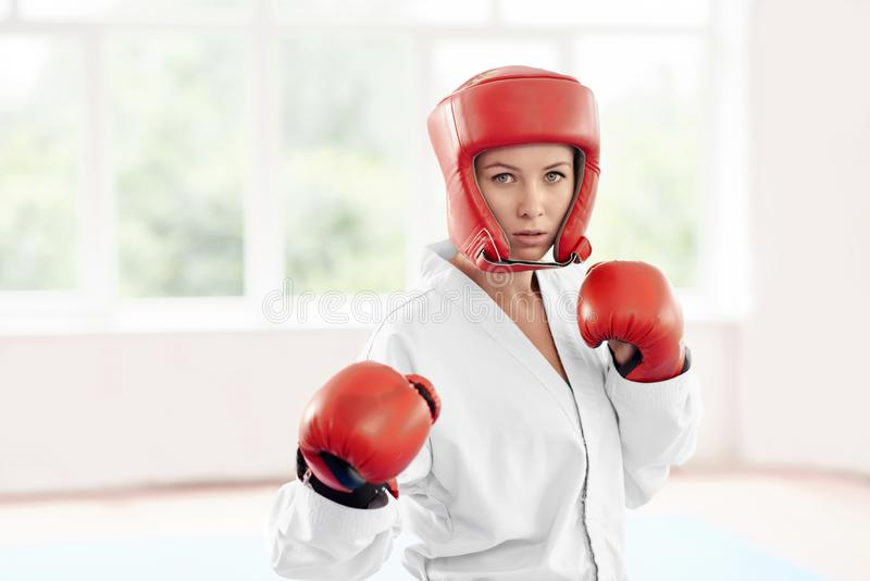 Professional female karate fighter standing in position against big window. stock image