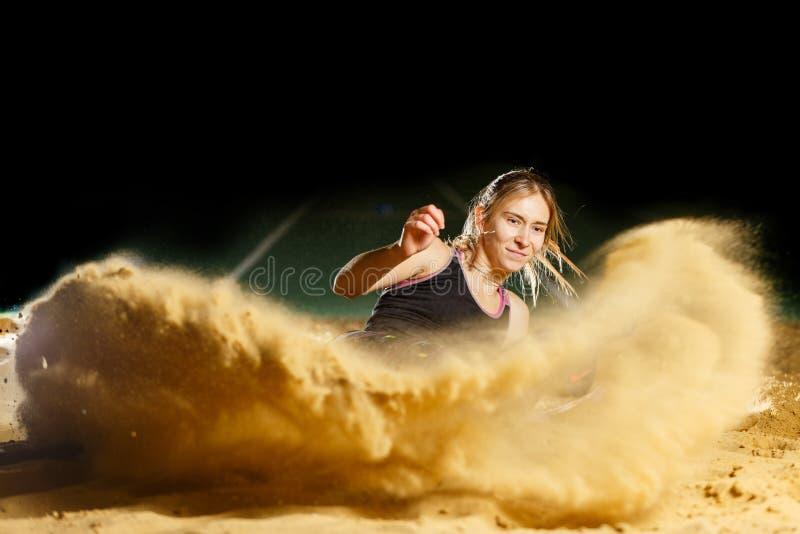 Female long jump athlete landing in sandpit. Professional female long jump athlete landing in sandpit stock images