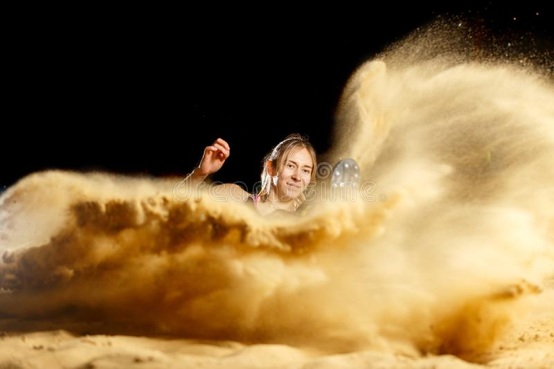 Female long jump athlete landing in sandpit. Professional female long jump athlete landing in sandpit royalty free stock photography