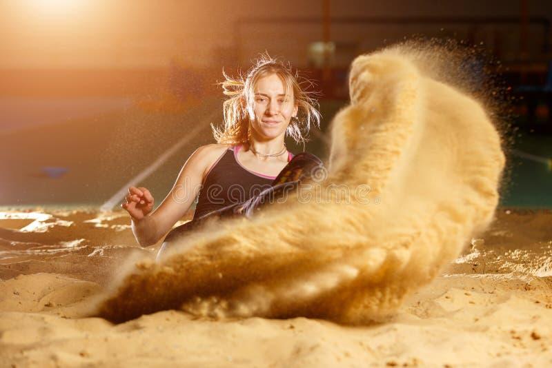 Female long jump athlete landing in sandpit. Professional female long jump athlete landing in sandpit stock photos