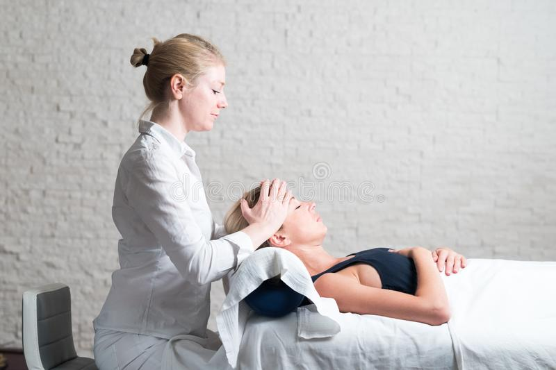 Professional female masseur giving relaxing massage treatment to young female client. Hands of masseuse on forehead of royalty free stock photos