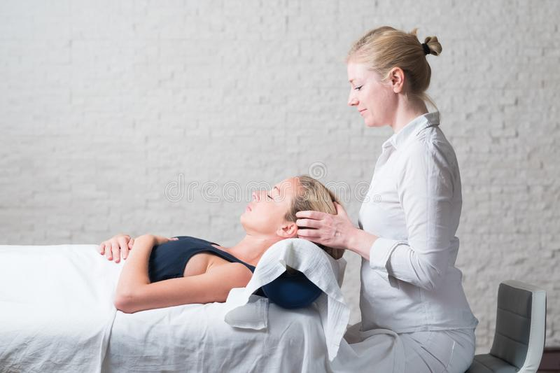 Professional female masseur giving relaxing massage treatment to young female client. Hands of masseuse on forehead of stock image
