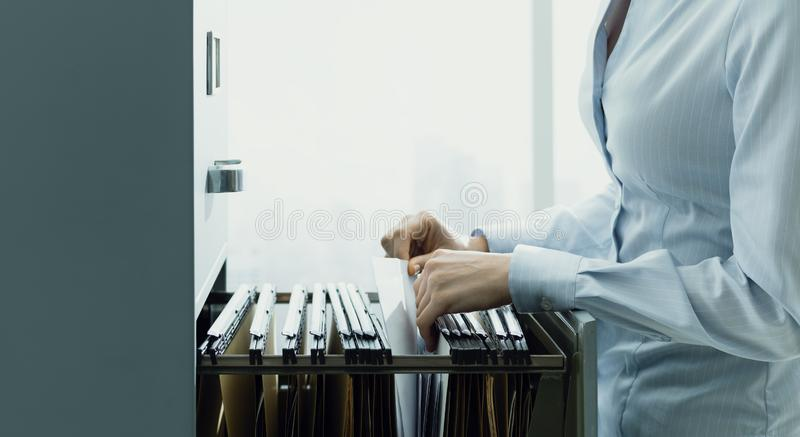 Office clerk searching files in the filing cabinet. Professional female office clerk searching files and paperwork in the filing cabinet stock image