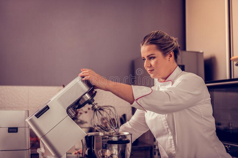Professional female pastry chef using kitchen machine stock photography