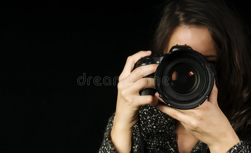 Professional Female Photographer. /Photo-Journalist Composing her Shot stock image