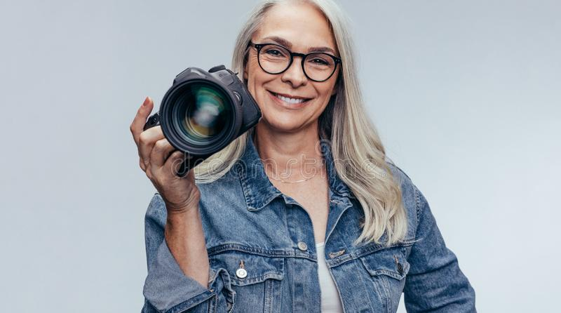 Professional female photographer with dslr camera. Confident senior woman in casuals holding a dslr camera on grey background. Professional female photographer stock photography