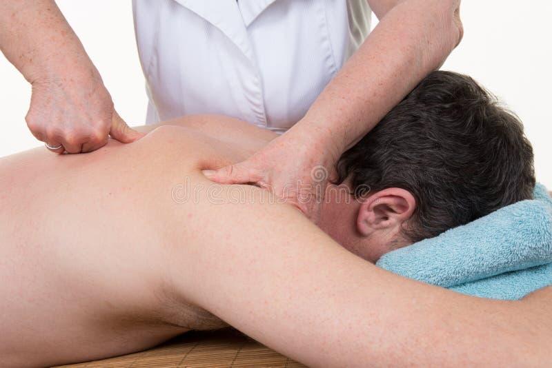 Professional female physiotherapist giving shoulder massage at hospital stock photo