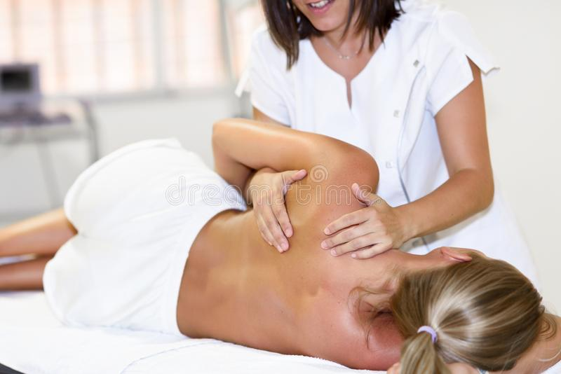 Professional female physiotherapist giving shoulder massage to b stock photos