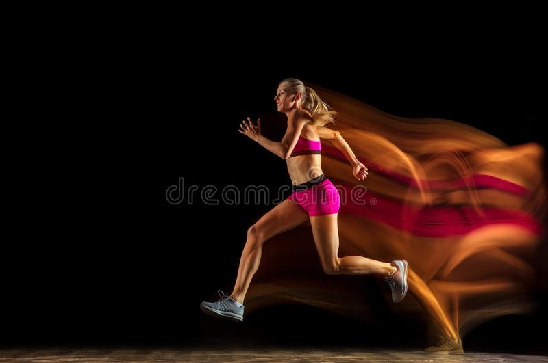 Professional female relay racer training on black studio background in mixed light stock photography