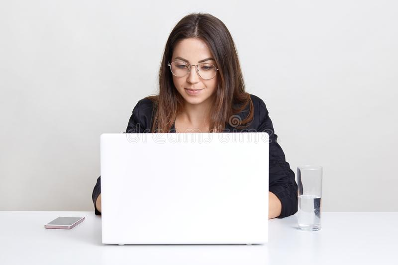 Professional female software developer works on laptop computer, keyboards information, connected to wireless internet, works with stock images