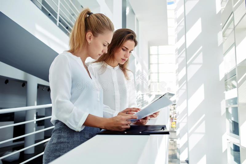 Professional female staff analyzing strategy of their work on paper documents while standing in office interior,. Successful women financiers discussing ideas royalty free stock photos