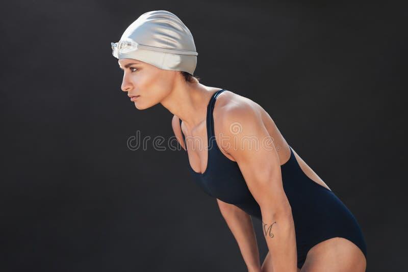 Professional female swimmer on black background. Professional female swimmer with goggles and a hat on black background stock images