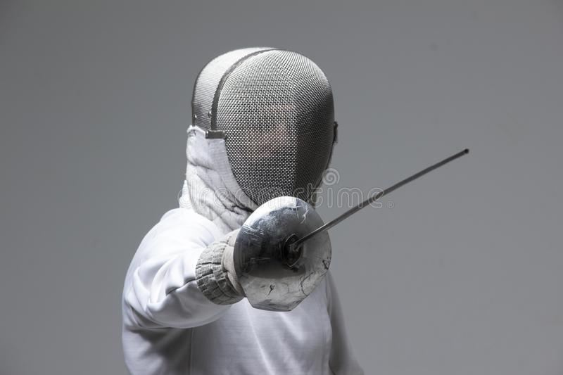 Professional fencer in fencing mask attacking on grey background. Professional fencer in fencing mask practising with sword on grey background stock photos