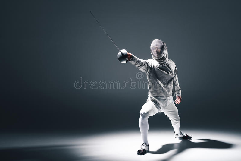 Professional fencer in fencing mask with rapier standing in position. On grey stock photos