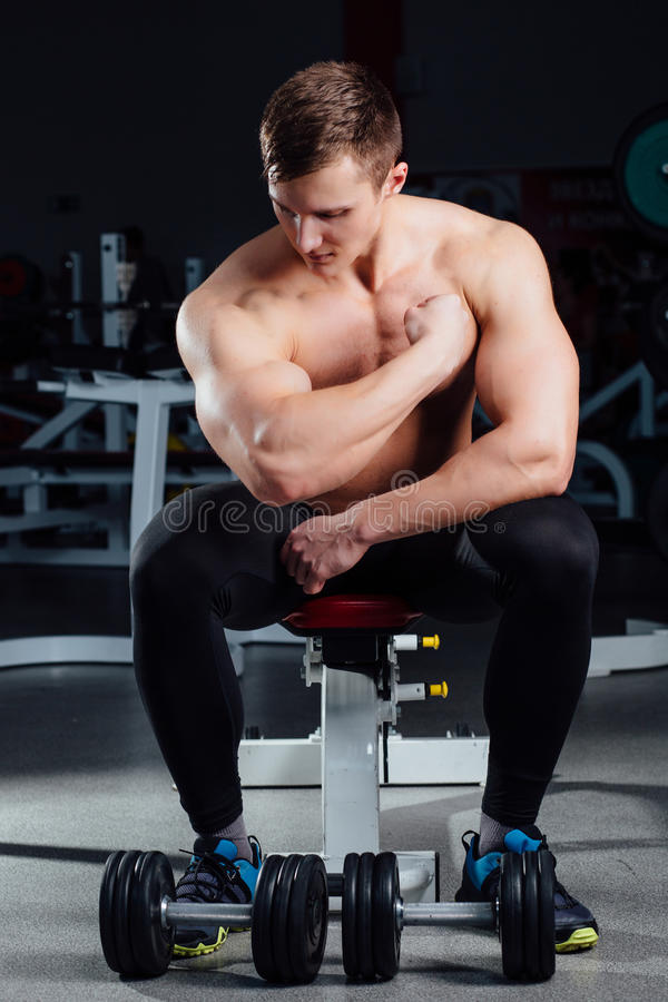 Professional fitness bodybuilder sitting on the bench and demonstrates muscles of your body after a workout, at gym. Big Confident muscular man training stock photos