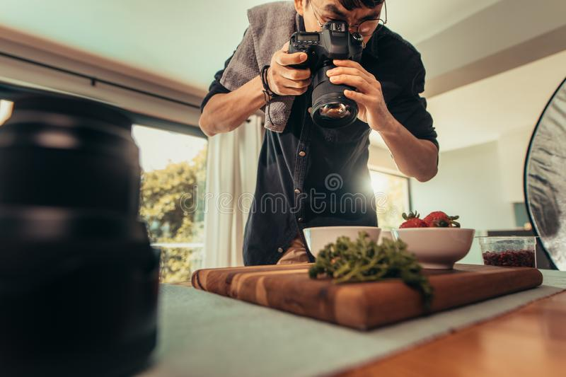 Professional food photographer in studio. Photographer taking pictures of food in studio. Professional food photographer making food shot for advert royalty free stock images