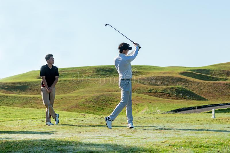 Professional golfer asian two man approach on the tee off for swing and hitting golf ball and looking fairway in course. Hobby in royalty free stock photography
