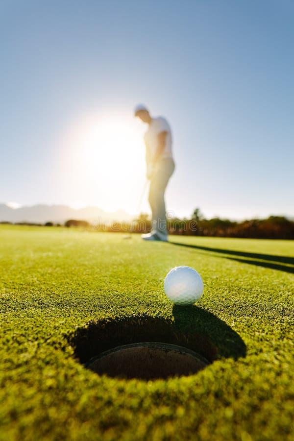 Professional golfer putting golf ball royalty free stock image