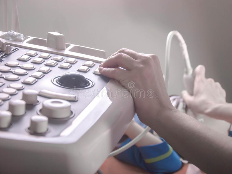 Doctor's hands, using an ultrasound scanner, examine the patient's organs. Professional gynecologist performing breast examination for her patient stock photos