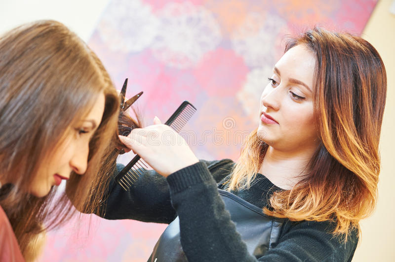 Professional hair stylist with scissors and comb stock image