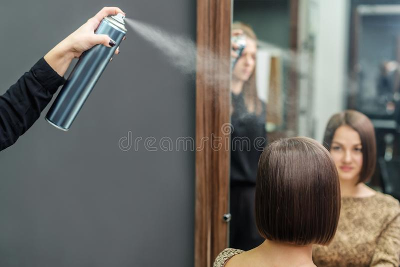 Professional hairdresser applying hair spray on short hairdo in beauty salon. Kare hairstyle royalty free stock image