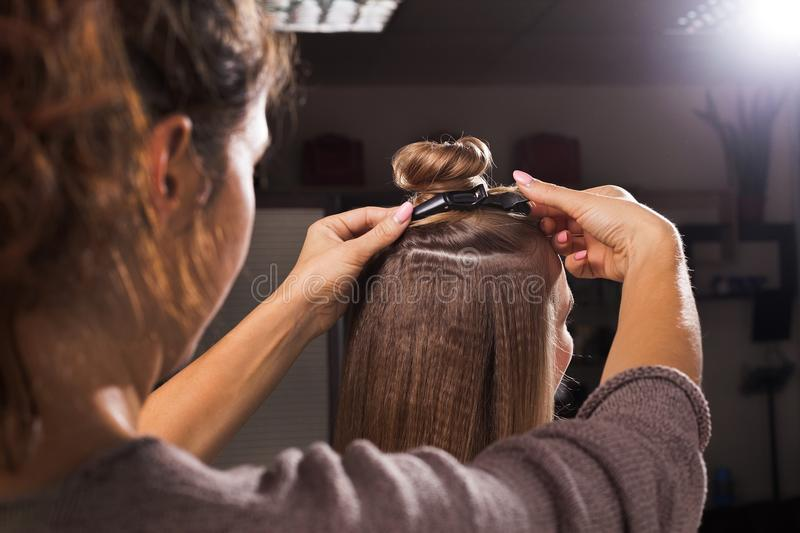 Hairdresser clipping a hairdo with a topknot. Professional hairdresser clipping a hairdo with a topknot using a hairpin to a young women in a beauty salon stock photography