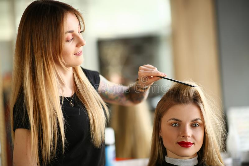 Professional Hairdresser Combing Girl Client Hair. Young Hairstylist Making Haircut with Hairbrush for Female with Long Blonde Hairstyle. Beautician Styling royalty free stock image