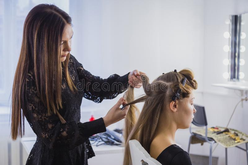 Professional hairdresser doing hairstyle for young pretty woman with long hair royalty free stock photography