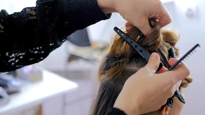 Professional hairdresser doing hairstyle for young pretty woman. Professional hairdresser, stylist combing hair of female client and using barrette for fixing stock photos