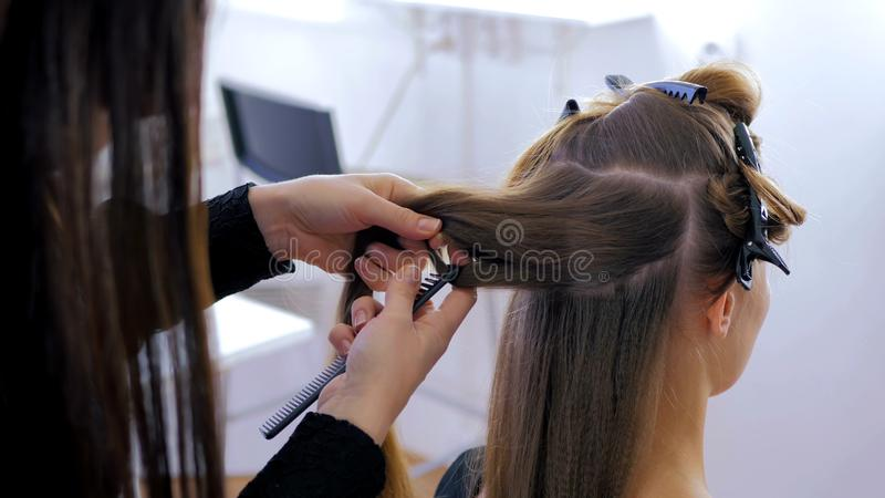 Professional hairdresser doing hairstyle for young pretty woman. Professional hairdresser, stylist combing hair of female client and using barrette for fixing stock photography