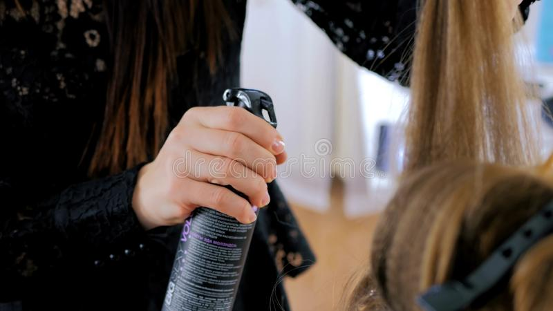 Professional hairdresser doing hairstyle for young woman and using hair spray royalty free stock photo