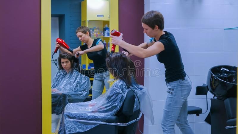 Professional hairdresser drying client hair stock photos