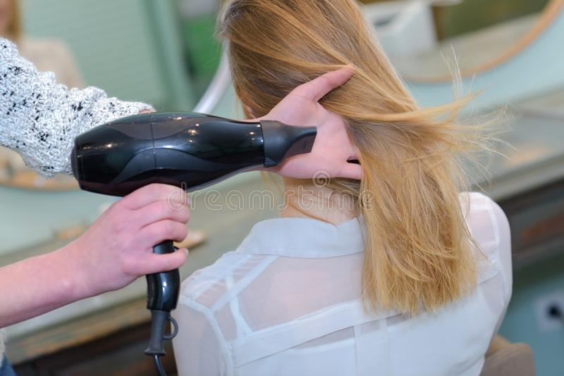 Professional hairdresser drying hair royalty free stock photography