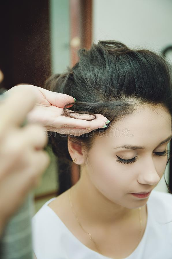 A professional hairdresser makes a festive hairstyle for the girl. Close-up royalty free stock image