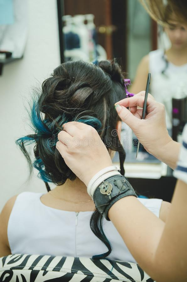 A professional hairdresser makes a festive hairstyle for the girl. Close-up stock image