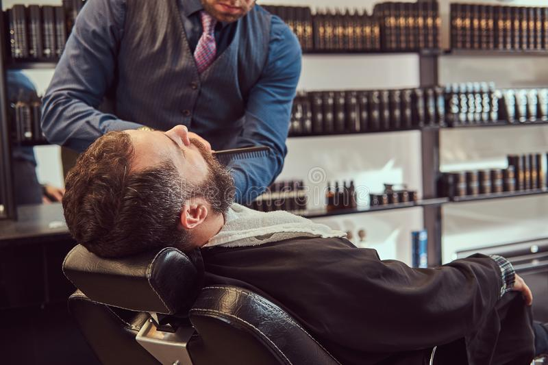 Professional hairdresser modeling beard with scissors and comb at the barbershop. Bearded male sitting in an armchair in a barber shop while hairdresser stock images