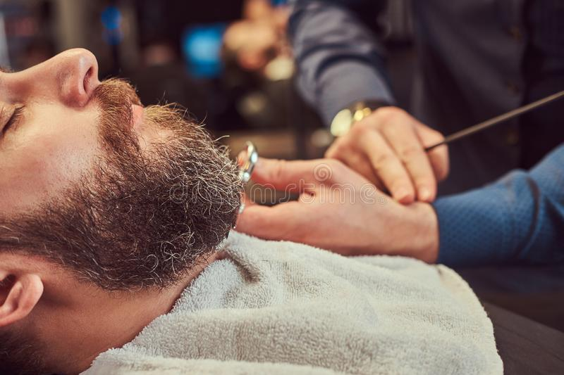 Professional hairdresser modeling beard with scissors and comb at the barbershop. Close-up photo royalty free stock photography