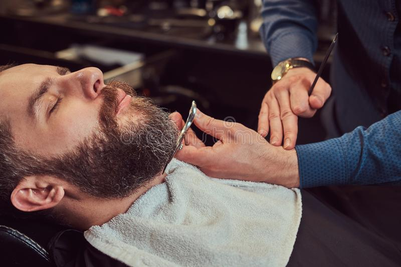 Professional hairdresser modeling beard with scissors and comb at the barbershop. Close-up photo stock image