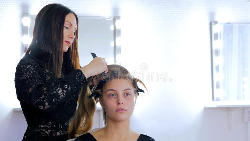 Professional hairdresser doing hairstyle for young pretty woman. Professional hairdresser, stylist combing hair of female client and using barrette for fixing stock image