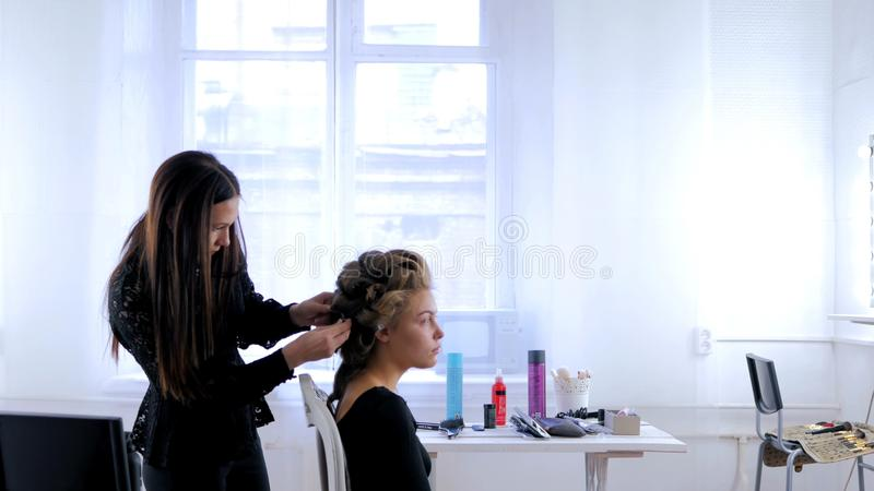 Professional hairdresser doing hairstyle for young pretty woman stock images