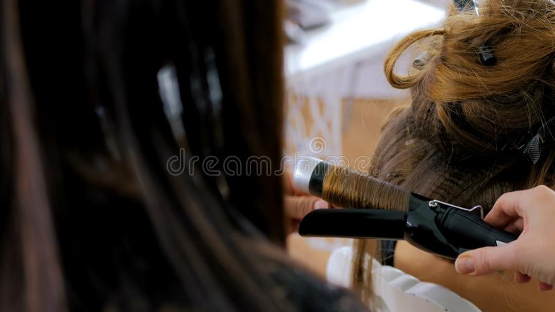Professional hairdresser doing hairstyle for woman - making curls royalty free stock photography