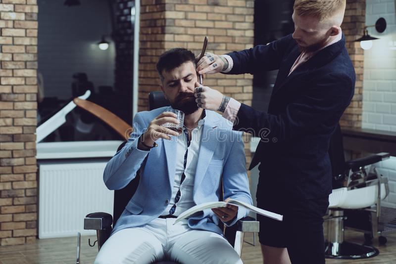 Professional hairstylist in barbershop interior. Male client getting haircut by hairdresser. Balm on dry body parts to royalty free stock image